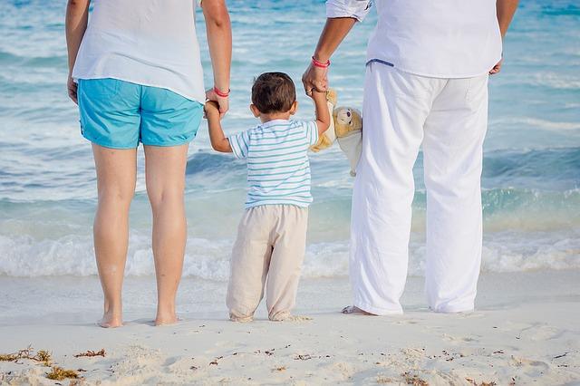 ビーチで佇む父と母、息子